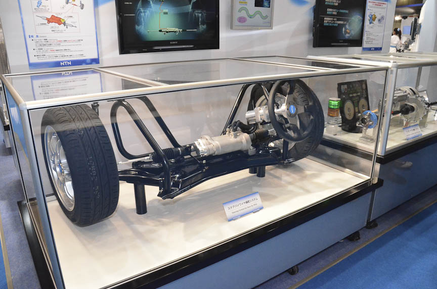 NTNのステアバイワイヤ操舵システム。ステアリングホイールは電気的に操舵機構につながっているだけで、機械的にはつながっていない。操舵はすべてモーターが受け持つが、自動的にトー角を制御することで、人間が操舵するよりも操縦安定性と燃費が向上すると言う。バックアップ用の小型モーターも搭載する