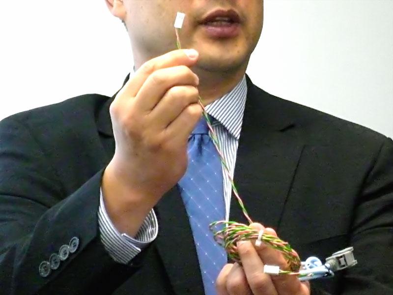 右手で引っ張っているのが、BroadR-Reach用のケーブル。左手に持っている水色のものが従来のLVDSケーブルである