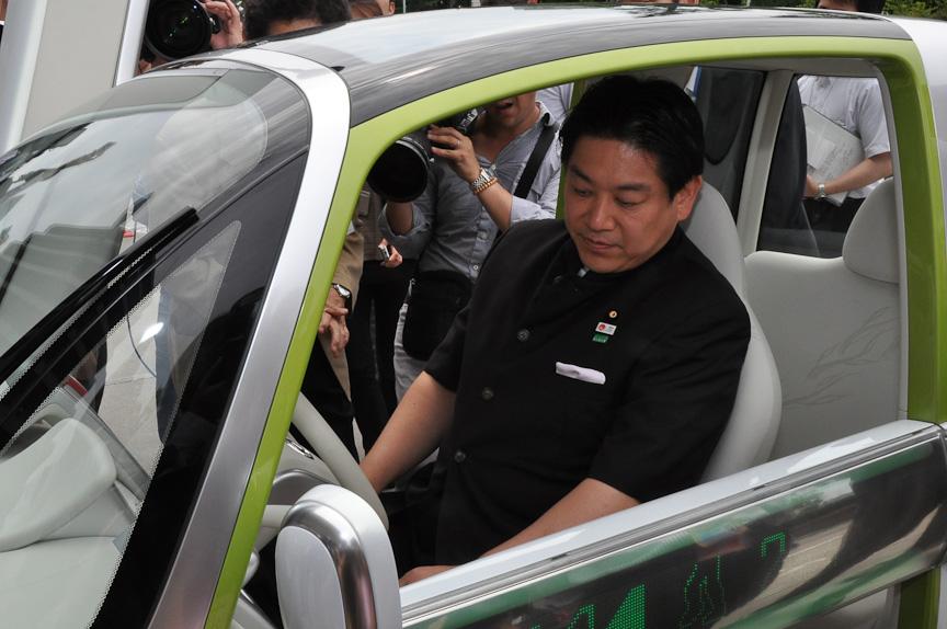 ダイハツのPICOの運転席に乗り込み、各種操作の説明を受ける羽田国交大臣
