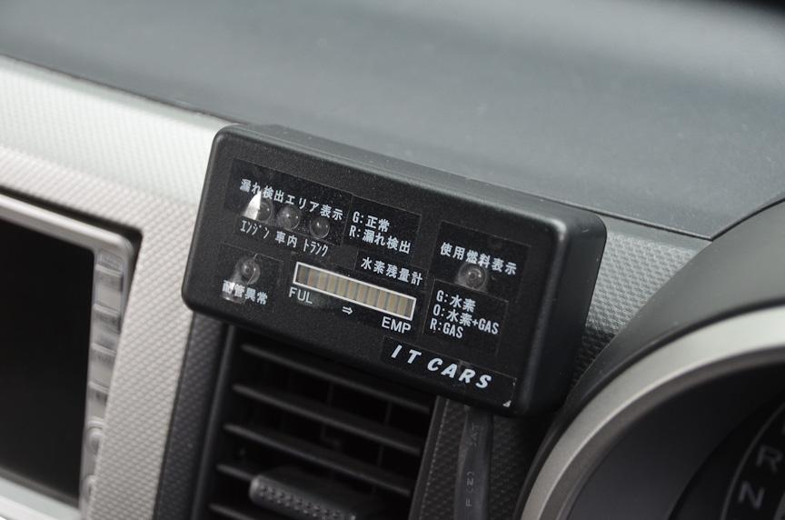 公開されたワゴンRのコンバート車両。ラゲッジスペースに水素タンクを搭載し、左のリアクォーターウィンドーが水素充填口になっている。エンジンルームは一見するとノーマルだが、よく見るとインジェクターが増設されている。コックピットには燃料切り替えスイッチと、水素残量計や使用している燃料のモニターが設置される。モニターは水素使用時に緑、ガソリン使用時に赤、併用時にオレンジに点灯する