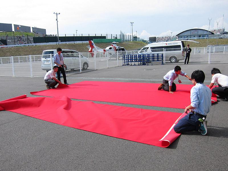 メディアセンター入り口付近で赤絨毯を敷く作業