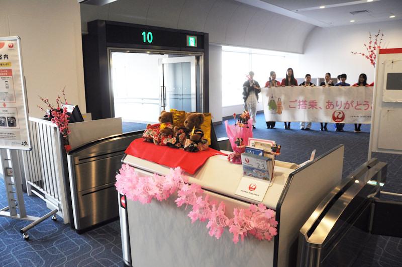 """ひなまつりフライトとなるJAL1487便の搭乗口付近は、手作りの""""おしごと紹介""""ポスターや桃の花、ひな人形などで飾られた。"""
