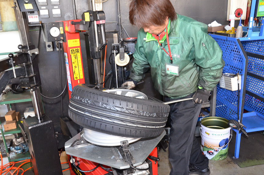 タイヤチェンジャーでホイールにタイヤをはめる