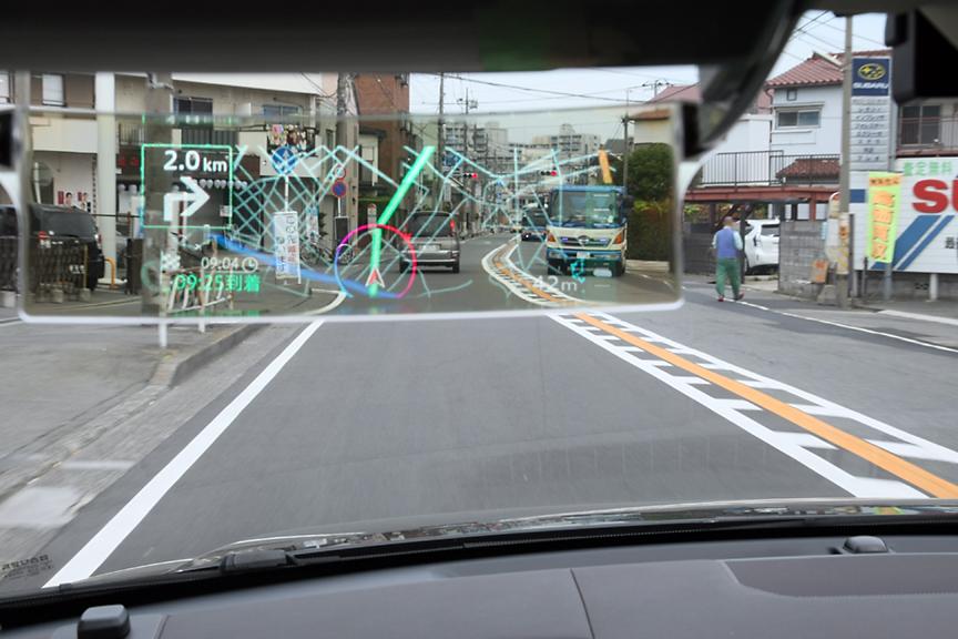 新型サイバーナビ試乗車のため、撮影用として助手席側にもAR HUDユニットが取り付けられていた。撮影のため明るさは最大に、また運転席側と異なる角度で撮影している。新型サイバーナビとの組み合わせでは、情報量も増えながら、より整理された感じ。ちなみに写真だとHUDのコンバイナー部(透明なパネル部分)に地図が描かれているように見えるが、レーザービームにより投影方式のため、3m先に37インチ相当(90cm×30cm)の画面が広がるよう調整されている。この部分の仕様などは、2012年モデルと同様