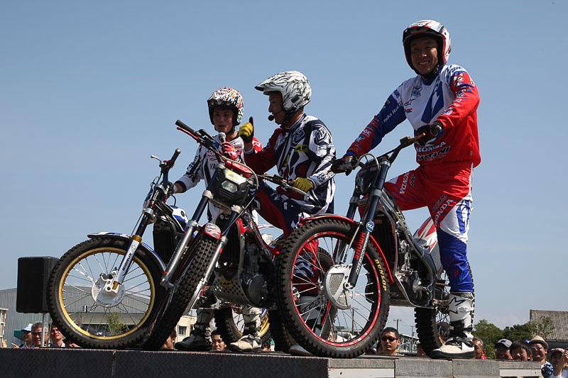 会場でもっとも注目を集めた「トライアルデモンストレーション」を披露した3人の選手。中央はMCも務めたトライアルデモンストレーターの小林直樹氏。左が2012年度MFJ全日本トライアル選手権シリーズランキング1位の黒山健一氏、右が同2位の小川友幸氏