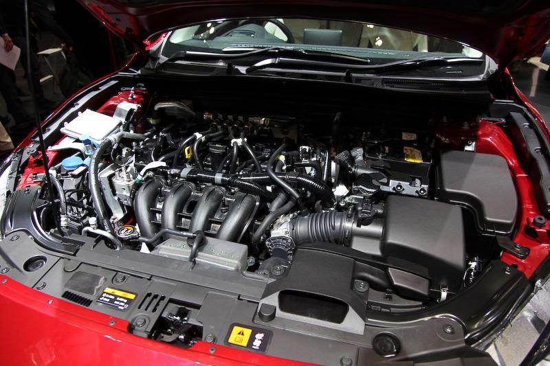 75Lの容量を持つトランク内のCNGタンクから配管を伝わり、エンジンルームの専用インジェクター(4本)にCNGを供給。インテークマニホールド内にCNGを吹くことによって、エンジンが燃焼する。エンジンルームに向かって左側に給ガス口がある。CNGはオクタン価が高く、圧縮比の高いSKYACTIVエンジンと相性がよいという。ガソリン/CNGの切り替えスイッチはシフトレバー前方にあり、走行中の切り替えも可能。現在はイラストだが、CNGの残量計も兼ねている