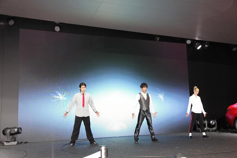 ステージ上での3人のダンサーによる激しいダンスパフォーマンスでプレスブリーフィングがスタート
