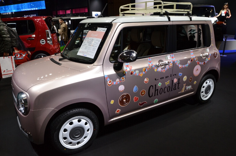 アルト ラパン ショコラの展示車は、ルーフラック、ドアハンドルガーニッシュ、メッキ仕上げのドアミラーカバーなどを装着。ドアパネルなどにあしらわれたステッカーは撮影用でオプション品として販売されているものではない