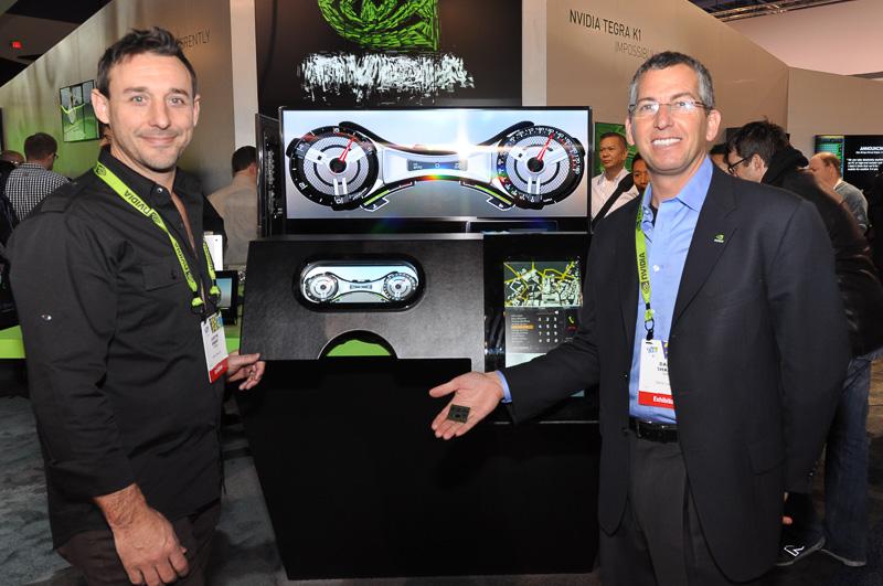 NVIDIA オートモーティブ部長のダニー・シャピーロ氏(右)と、同 オートモーティブ・ミドルウェア担当ディレクター ジャスティン・イーバート氏(左)。ダニー・シャピーロ氏が手に持っているのがTegra K1だ。後方に見えるのは、Tegra K1で実現するデジタルコクピットのサンプルデモで、ジャスティン氏はその開発ツールなどを担当している