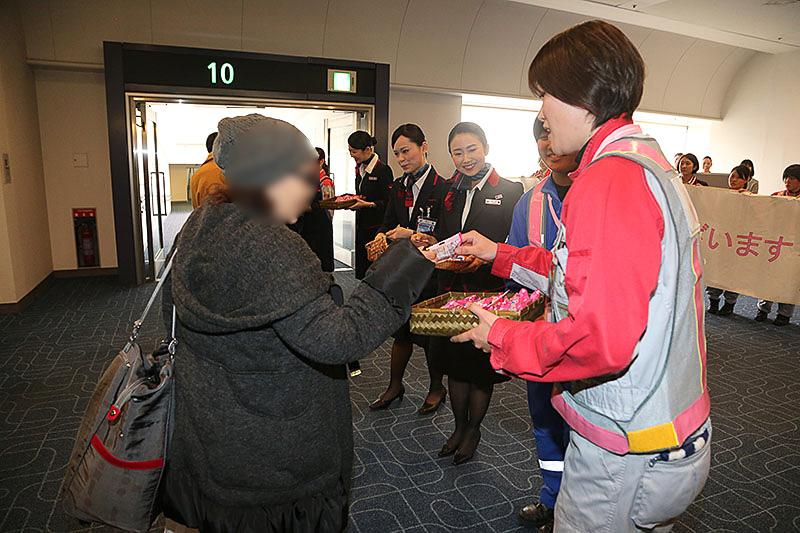乗客1人ひとりにプレゼントを渡すスタッフ