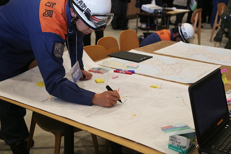 消防隊員は食糧が確保可能な施設や通行可能な道路の周囲状況などを逐次地図に書き込んでいた