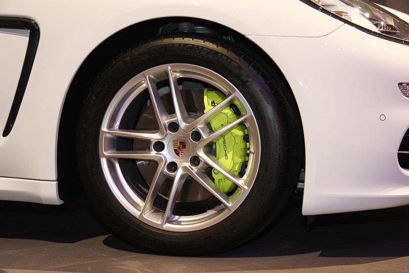 アシッドグリーンのブレーキキャリパーは外観上の大きな特徴。純正装着品はフロント:245/50 ZR18、リア:275/45 ZR18のタイヤと18インチ「パナメーラ Sホイール」の組み合わせだが、ホワイトの展示車は19インチ「パナメーラ ターボIIホイール」を装着