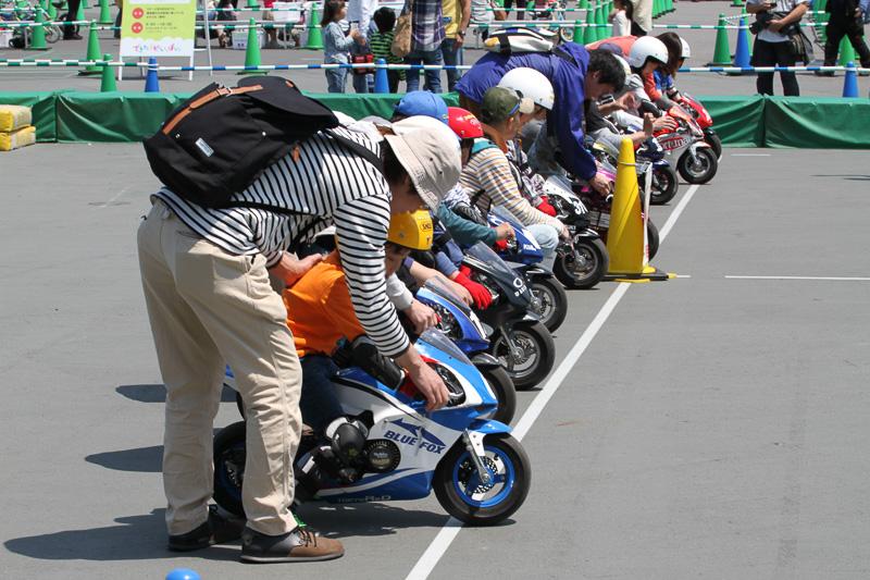 ポケバイ親子教室。小さな子供が小さなバイクに、大きなヘルメットをかぶって乗る姿が可愛らしい