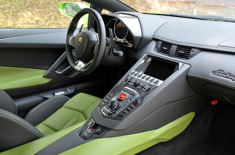 レザーやカーボンが多用されたレーシーかつ上質なインテリア。アヴェンタドールのシフト操作は、センターコンソールの後方側にある「R(リバース)」「M(マニュアル)」ボタンおよびパドルシフトで行う。また、センターコンソールに用意されるスイッチで「STRADA」「SPORT」「CORSA」の3モードの走行モードを選択できる