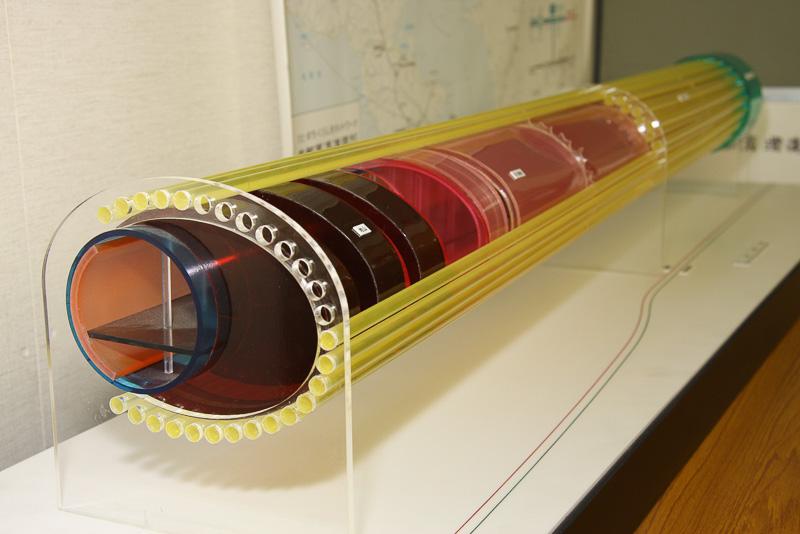 取材の集合場所となった「横浜環状北線インフォプラザ」に展示されていたトンネル拡幅工事のイメージ模型。直径12.3mの本線シールドトンネルを、拡幅部終端では高さ15.5m、幅21.5mの楕円形に拡幅。パイプルーフか放射状に広がる独特の工法についてもイメージしやすい