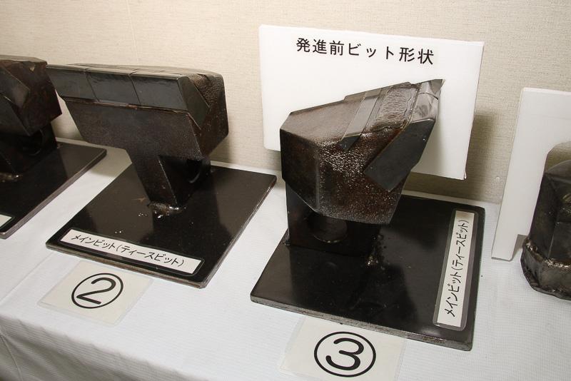 横浜環状北線インフォプラザには、シールドマシンのカッターフェイスに取り付けられていた「カッタービット」も展示されていた。左側に置かれた鋭角なフォルムの「メインビット」はそれほど減っていなかったが、右側にある、最初期に発進立坑のコンクリート壁を切り開いた「先行ビット」「ノムスト切削用先行ビット」は、白い展示プレートで表現されたに発進前の形状から摩耗して小さくなっていることが分かる