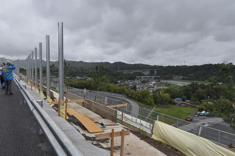 路肩の風景。将来的に遮音壁が設けられるためこの風景は見られなくなる。右奥の大きな橋が新小倉橋、その手前が小倉橋