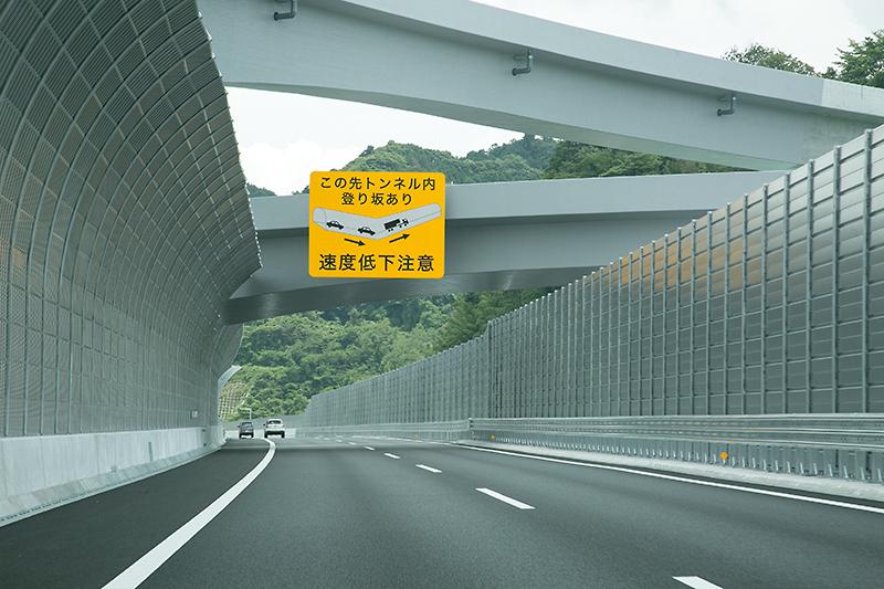 中央部が凹む、渋滞の起きやすいトンネルを注意する看板。看板が取り付けられているのは、将来は相模原ICになる部分