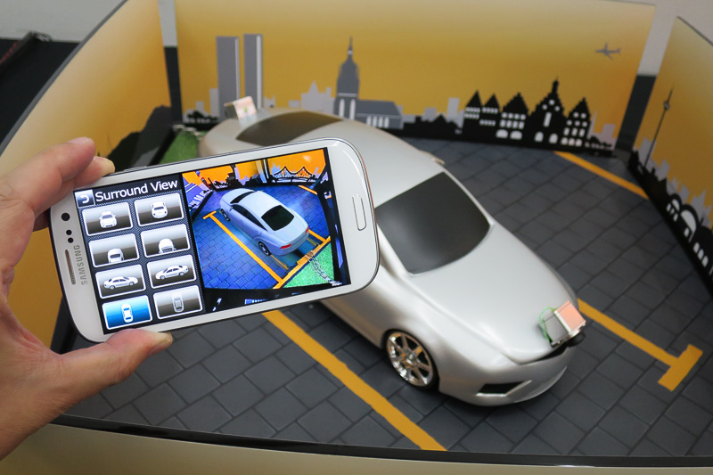 車両のアラウンドビュー画像をスマホでも表示するLTE接続のデモ。広角カメラで撮影した映像を使っているが、画像処理で離れた場所まで歪みなく表示している。スマホ上のアイコンでも操作可能