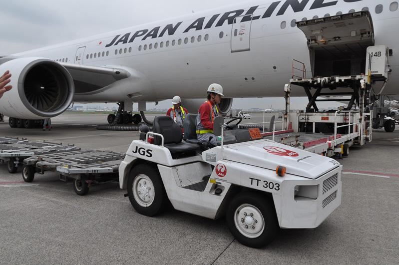 ハイリフトローダーが航空機に横付けされると、素早くトーイングトラクターが登場