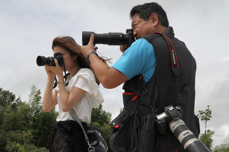 左手で筆者はレンズの先端、中川さんはレンズの根本を持っている
