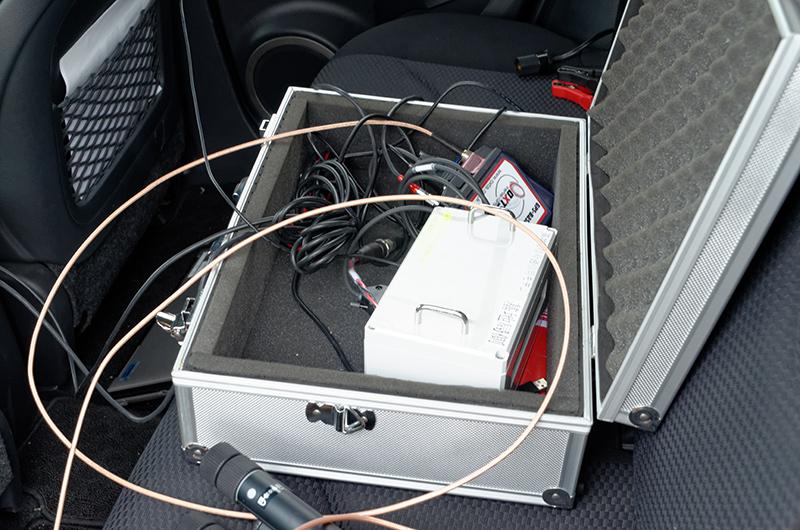 車両内にある基地局装置を介し、ルーフに設置されたアンテナで試験車両などに位置情報を無線送信する