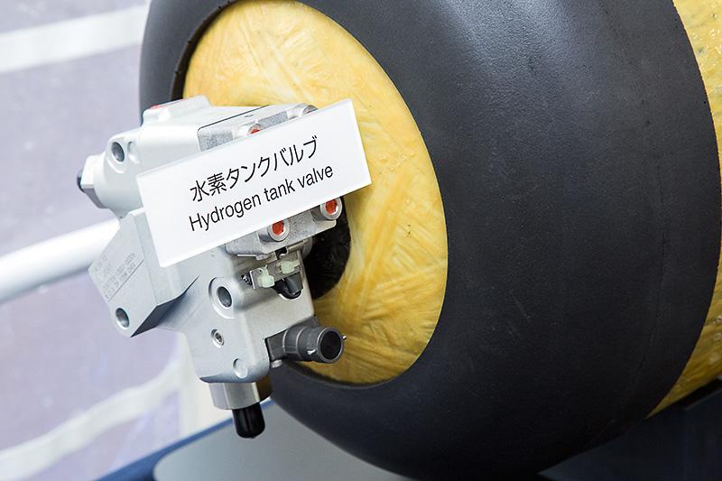70MPa(約700気圧)の高圧水素タンク。「漏らさない」「検知して止める」「漏れた水素を溜めない」との思想のもと、内層にプラスチックライナー、中層に炭素繊維強化プラスチック、表層にガラス繊維強化プラスチックを使う3層構造として強度を高めた。万が一の水素漏れの対策として、タンクに水素漏れを検知する検知器を搭載するとともに、車外に拡散しやすい構造を採用している