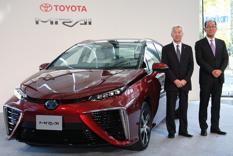 新型燃料電池車の「ミライ」と並んでフォトセッションに臨むトヨタ自動車 取締役副社長 加藤久光氏(左)とトヨタ自動車 製品企画本部 主査 田中義和氏(右)