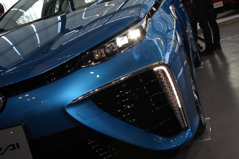 4灯LEDを使って横方向のワイド感を強調する超薄型ヘッドランプと、バンパー開口部に分割して縦型配置されるウインカー&クリアランスランプが力強い踏ん張り感を表現する。4灯LEDは車両外側の2つがロービームとなる
