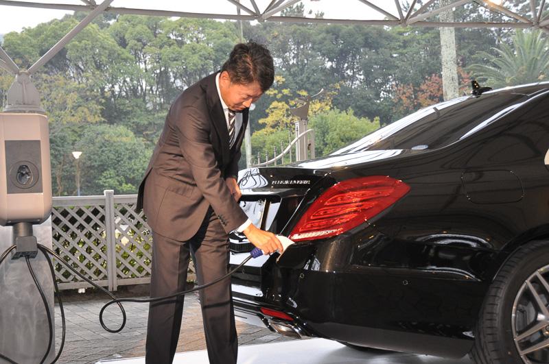 プラグイン充電を行うポーズの上野社長