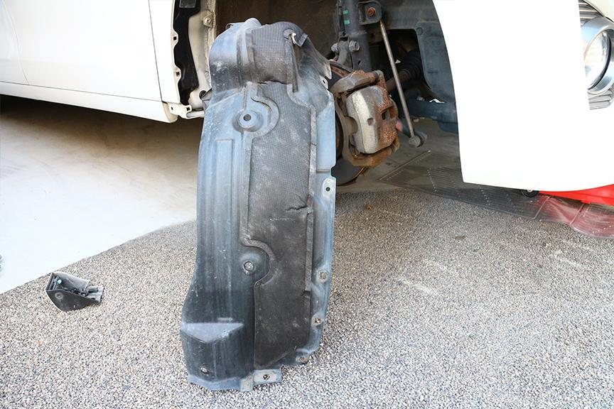 フロント右側のタイヤハウスカバーを外したところ。クルマ自体が大きいこともあり、こちらも大きく結構重い