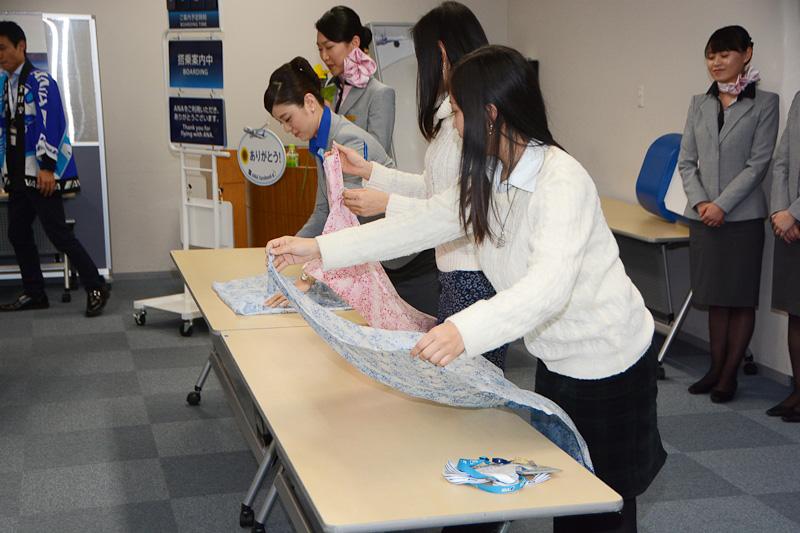 スカーフの巻き方講座。CAの2名は徳山さんが説明しながら江頭さんが実演