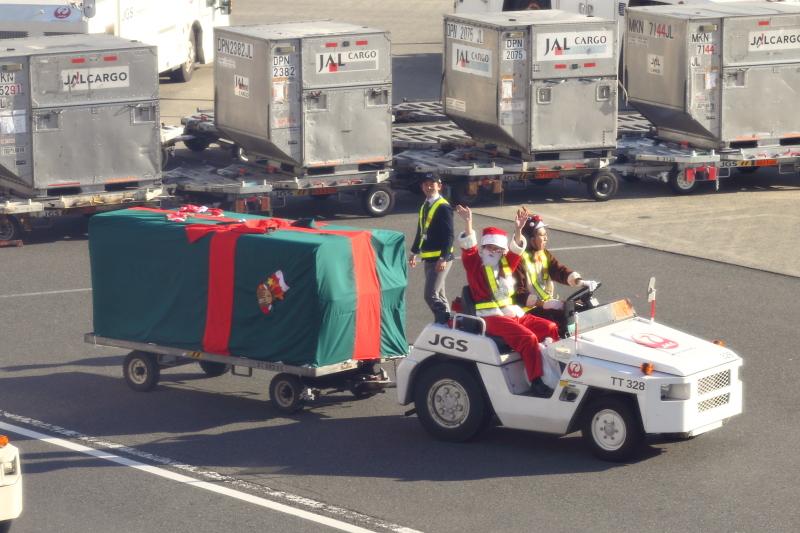 窓の外に見えてきたのはサンタとトナカイ、そしてトーイングトラクターに引かれた大きな大きなプレゼントだ。もちろんトーイングトラクターを運転するのはトナカイに扮したJALグランドハンドリングスタッフだ