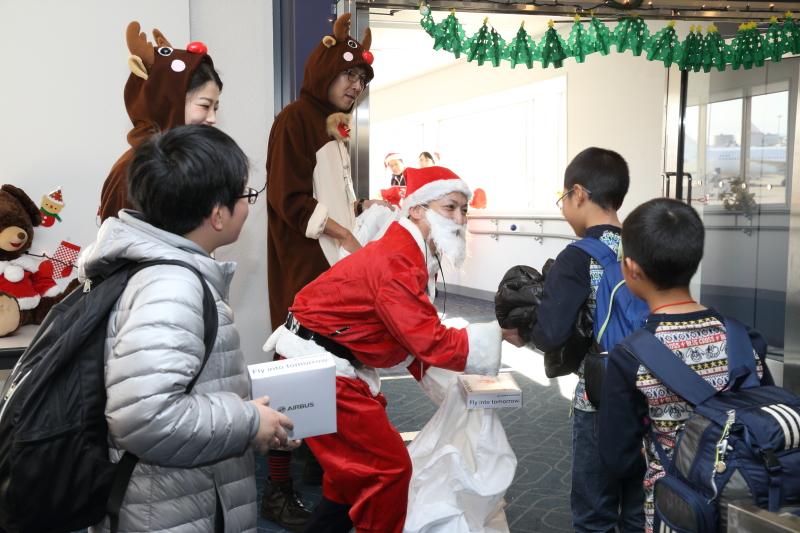 大人も子供もプレゼントを受け取りボーディングブリッジに進んでいく