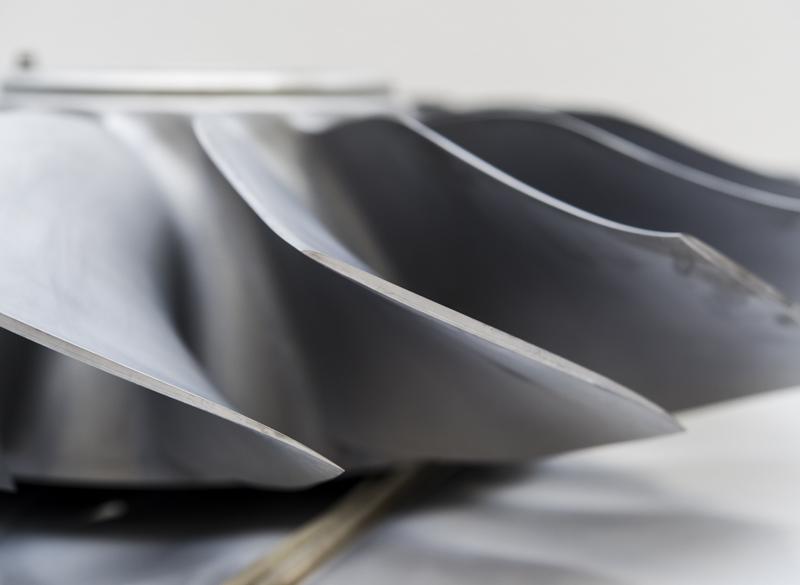 HF120のファンブレード(左・中)とファンOGV(右)。ブレードは鍛造チタンから削り出した一体型(ブリスク)で、近年のトレンドであるフォワードスウェプト形状となっている。OGVは世界初の短繊維複合材製