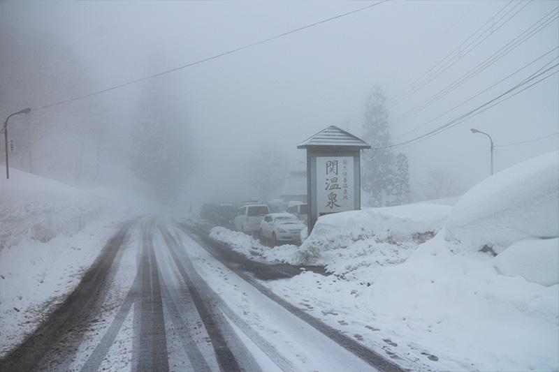 関温泉入り口。まだ冬の始まりなので、道路にはアスファルトが見えている。が、両脇に積み上げられた雪は既に1.5mを超えている