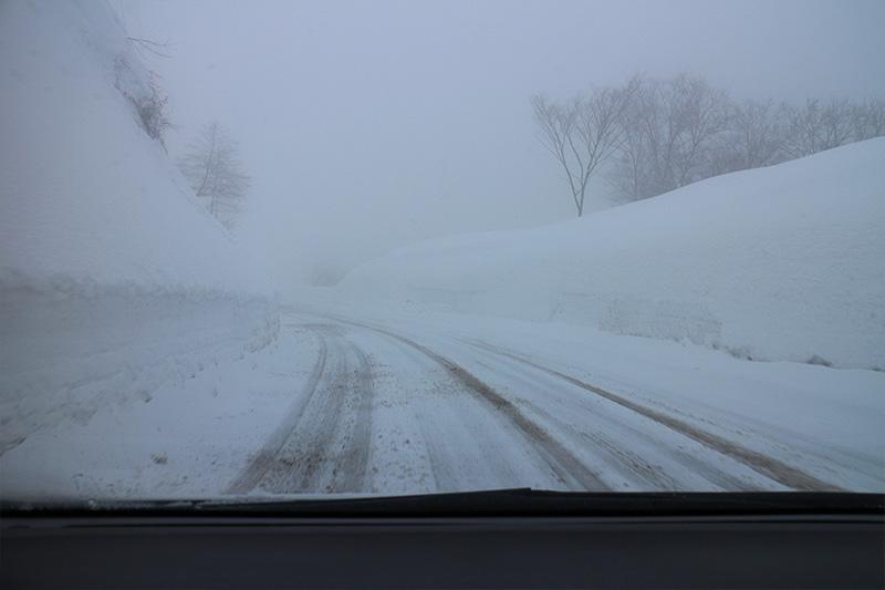 少し登ると、路面は圧雪状態に。アップダウンが続くため、道路には融雪剤や砂利が撒かれている