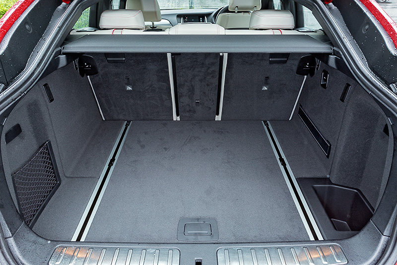 X4 xDrive35i M Sportのインテリア。ハイグロスブラック仕上げのセンターパネルやクロームの加飾が随所に配された上質な仕上がりになっている。X3と比べヒップポイントが前席で約20mm、後席で約30mm低くなるスペック。後席は40:20:40の3分割可倒式で、必要に応じてラゲッジルームの容量は最大1400Lまで拡大できる