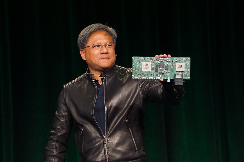 CESでのNVIDIAの記者会見でDRIVE PXを公開するフアン氏。DRIVE PXは12個の高解像度映像入力を持ち、2つのTegra X1を搭載することで、高度な演算性能を提供する