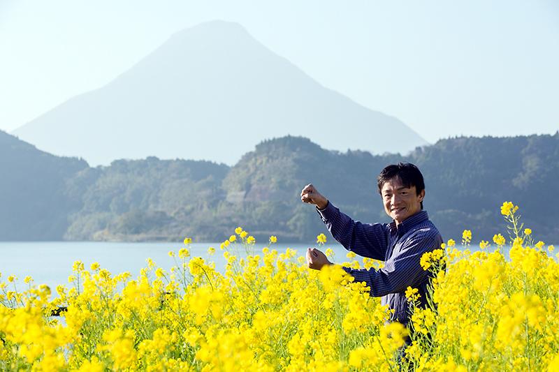開聞岳をバックに、池田湖畔の菜の花畑で「Be a driver.」。風は西から……以下略