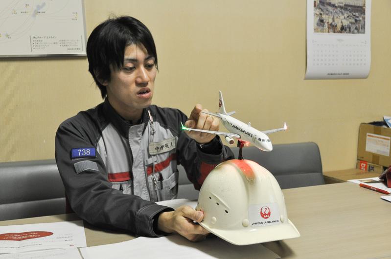 航空機の翼の効果について語ってくれた、JALエンジニアリングの中村英夫氏。青森空港のスタッフヘルメットにはすべて航空機が付いているわけではなく、ねぶた祭り参加用に作ったスペシャルバージョン。ねぶたで映えるよう、翼端灯なども点滅する