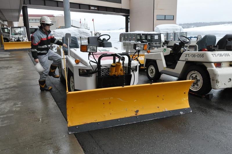 JALの保有するミニドーザ。航空機のまわりの雪を取り除くための、ドーザプレートが取り付けられている。ボンネットにはアップルマーク