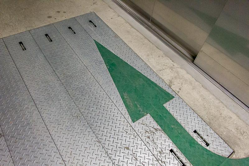 独立避難通路内の床にある出口サイン。矢印に従っていけば、外に出る前に避難する一時滞留所に行ける
