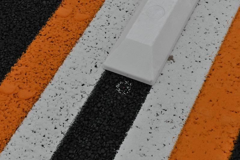路面にも県境の印はある。白丸で囲まれた赤点が県境の証