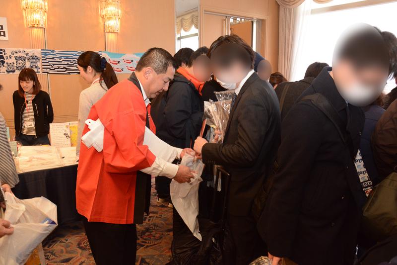 JAL会長の大西賢氏は、来場者の雑踏の中で、荷物を抱えた人を見つけてはビニールバッグを配布したほか、記念撮影にも応じていた