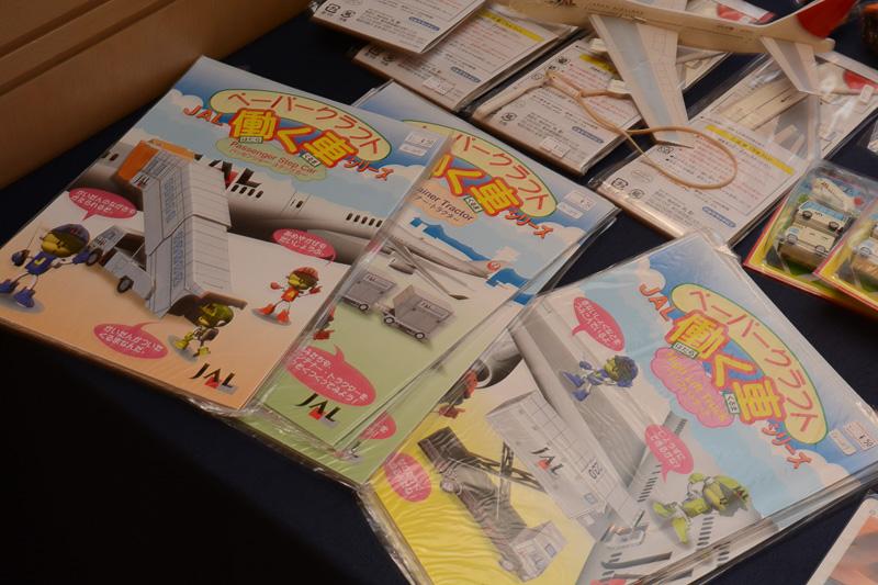 子ども向けのおもちゃコーナー。旧鶴丸塗装のペーパークラフトやJAL創立50周年記念のペーパープレーンなど多数用意