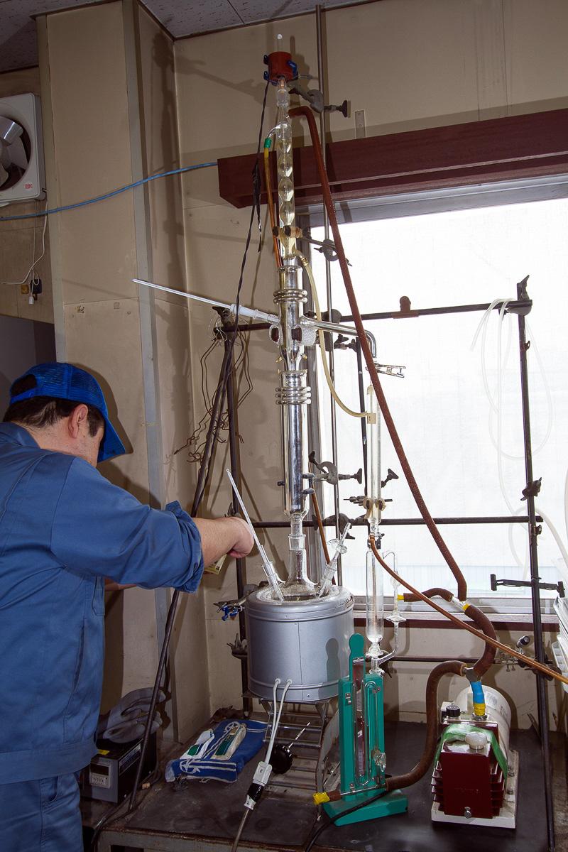 """これは""""ミニ蒸留塔""""ともいえる屋内の実験器具。本物の蒸留塔で作業を行う前に、こちらで原料液のテストを行い原料液の状態を確認する。他社から持ち込まれて蒸留を請け負う場合に加え、通常の製品開発でも原料液に含まれている内容物をしっかり把握しておくことが、製品の質やコストを左右する重要な要素となる"""