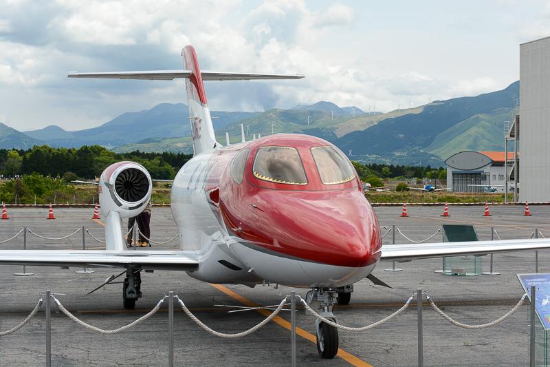 屋外展示された「HondaJet」。奥には阿蘇中岳から立ちのぼる噴煙