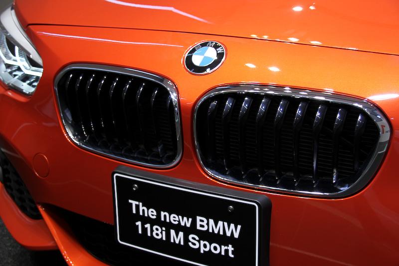 118i M Sport(ボディーカラーはヴァレンシア・オレンジ)。エクステリアでは、LEDハイ/ロービーム、LEDフロント・ターン・インジケータ、LEDスモール・ライト・リングからなる「LED ヘッドライト」を新たに標準装備(のぞく118i標準車)。またキドニー・グリルのデザインを一新するとともに、ワイドさを強調するL字型のリアコンビネーションライトも新採用