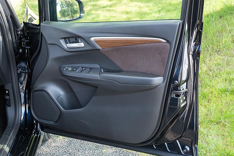 ドアトリムには木目調パネルとともにシート表皮と同じファブリックを採用